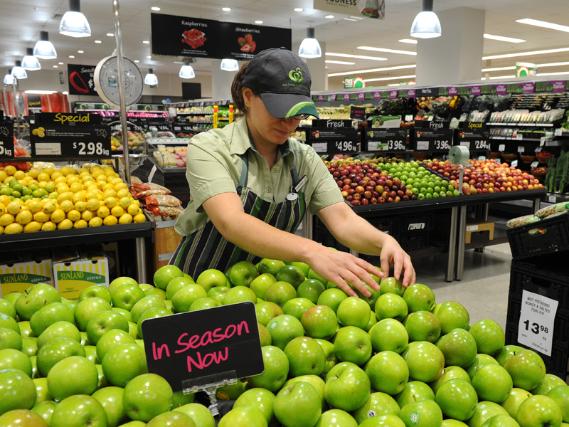An employee arranges fruit inside a Woolworths grocery store