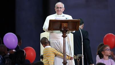 Beautiful moment ... former orphan boy Carlos hugs Pope Francis.