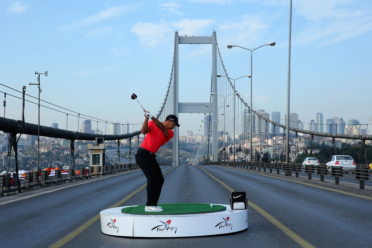 Tiger Woods launches a ball across Istanbul's Bosphorous Bridge, which links Asia and Europe.