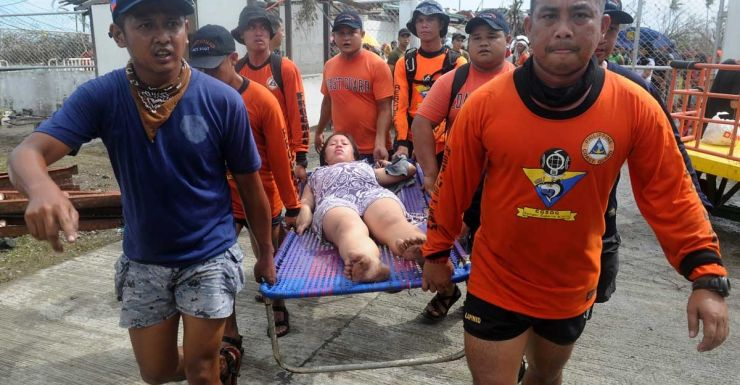 Rescue workers carry a woman about to give birth in Tacloban.