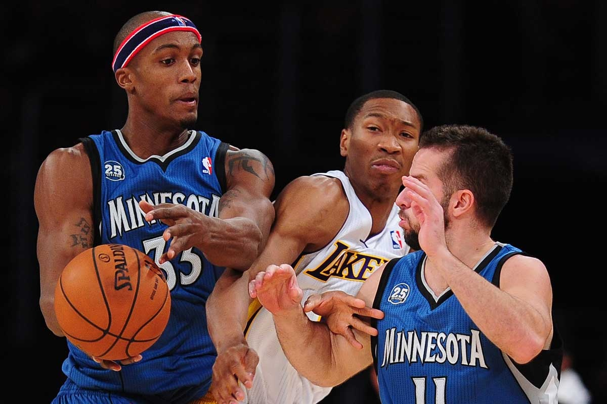 Laker Wesley Johnson is squeezed in by Dante Cunningham (left) and JJ Barea.