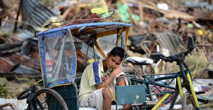 Typhoon Haiyan survivor rests surrounded by debris.