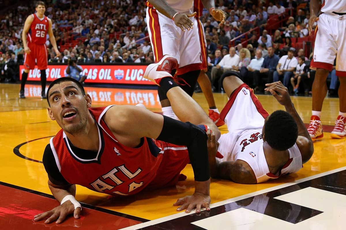 Gustavo Ayon of the Atlanta Hawks (left) after fouling Udonis Haslem.