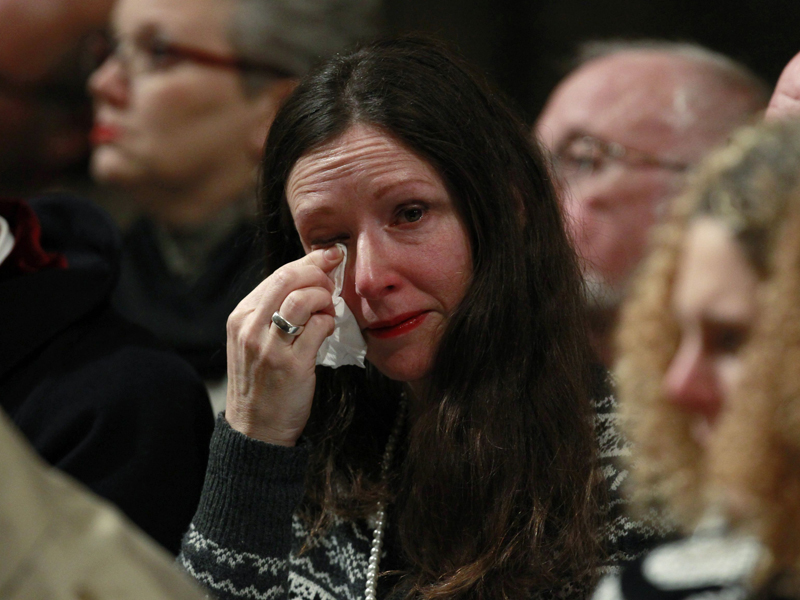 A woman wipes her eye during a service.