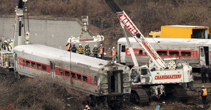 Cranes salvage the last car from from a train derailment in the Bronx