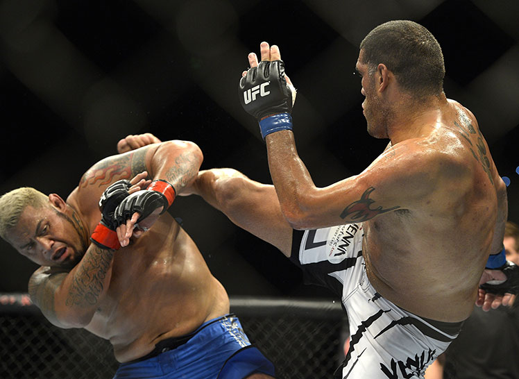 Mark Hunt (left) blocks an a high kick from Antonio Silva.