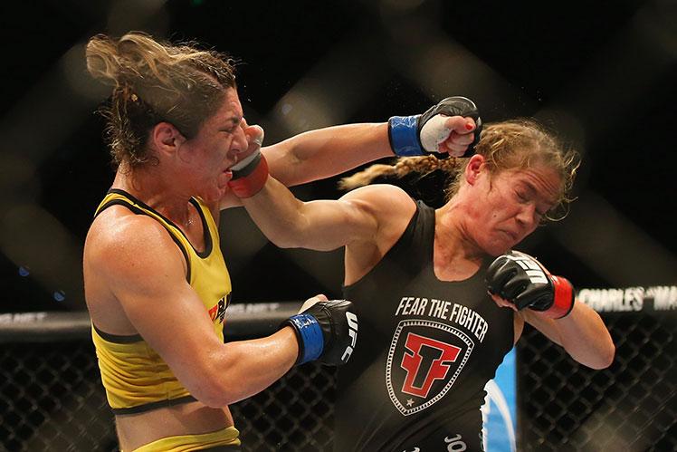 Bethe Correira (left) and Julie Kedzie trade blows in their UFC women's bantamweight bout in Brisbane.