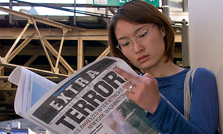 Chicago resident Shingo Lee reads the Extra edition of the Chicago Sun-Times printed after terrorist attacks on the United States.