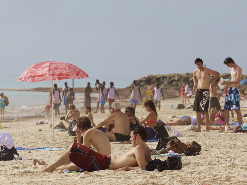 People lounge on the beach in Adelaide