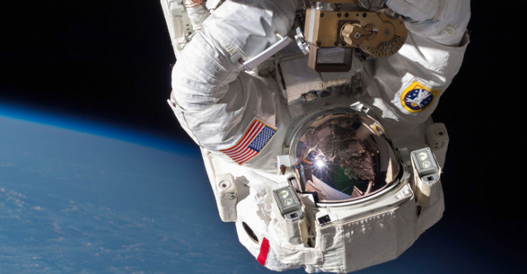 An astronaut performs a space walk on the International Space Station