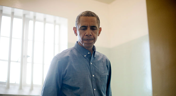 Barack Obama during a visit to the cell in which Nelson Mandela was imprisoned.