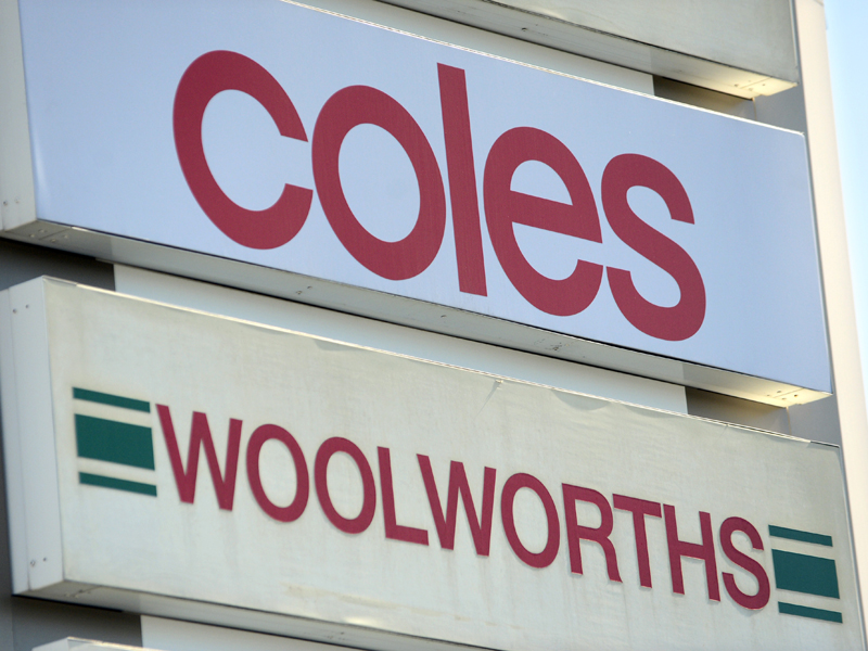 A sign with the logos of Coles and Woolworths supermarkets