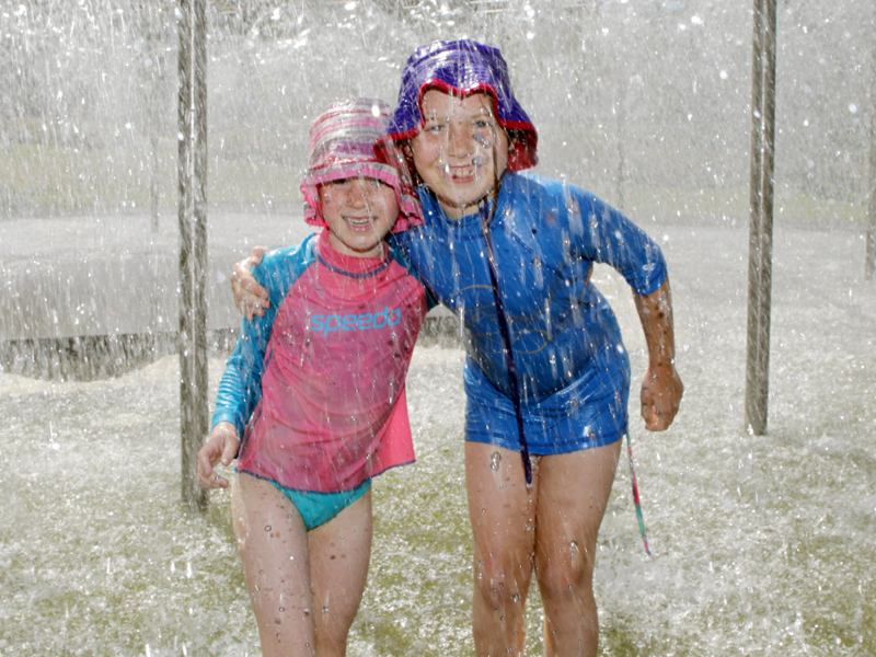 Two sisters escape the heat by playing under a fountain