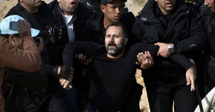 Egyptian policemen arrest a supporter of Mohamed Morsi