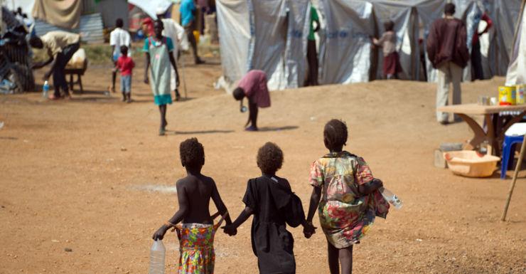 Three children walk through a UN camp