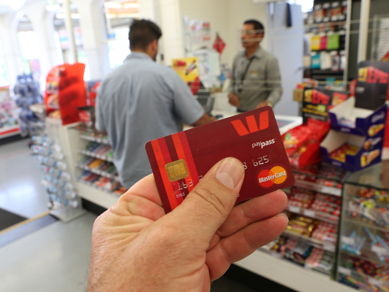 A customer using a tap-and-go credit card in a store