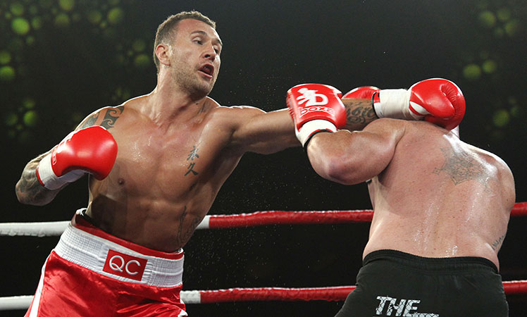 Quade Cooper (left) throws a left jab as Warren Tresidder ducks for cover in their cruiserweight bout in Brisbane.