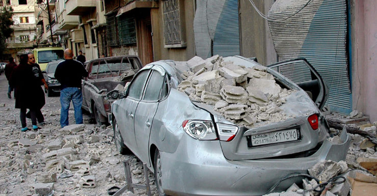 Damage at the site where people were wounded by rocket shells in Homs