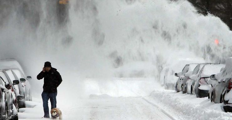 A man and his dog contend with blowing snow in Brooklyn.