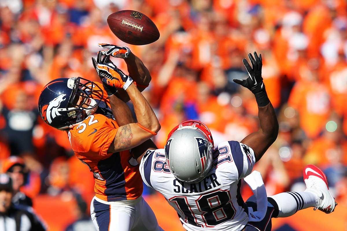 Tony Carter of the Denver Broncos (left) intercepts a pass.