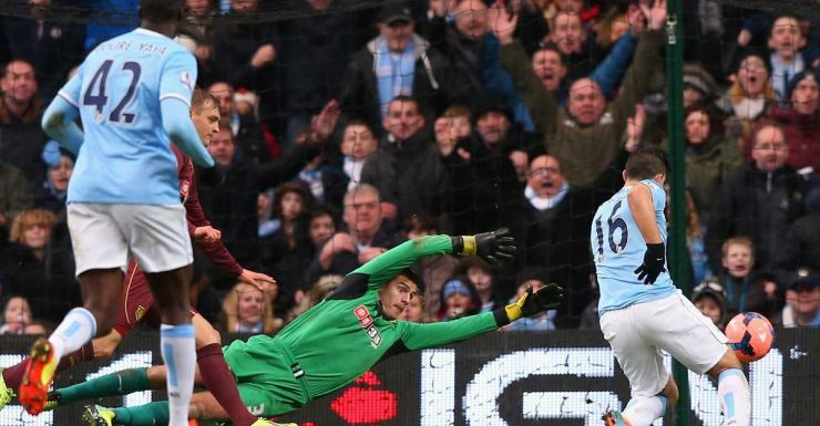 Manchester City's Sergio Aguero beats Watford goal-keeper Jonathan Bond.