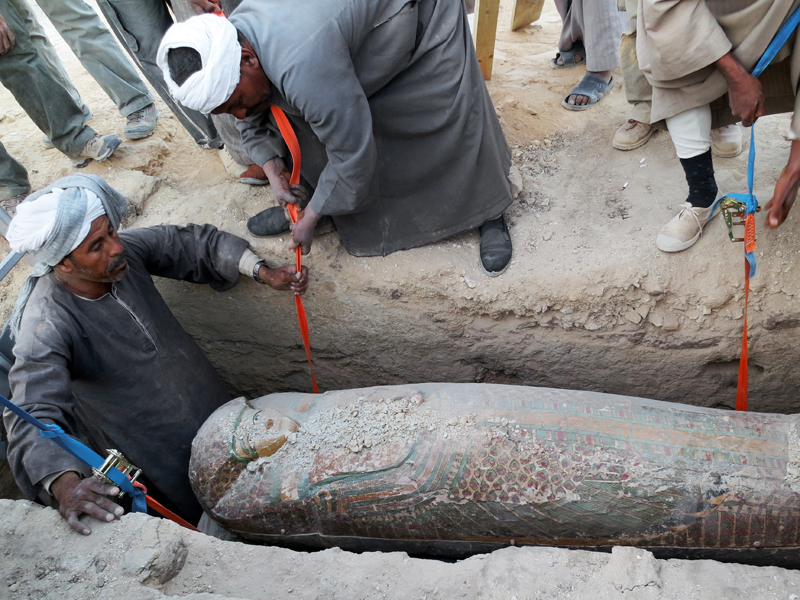 Egyptian men dig up a preserved wooden sarcophagus