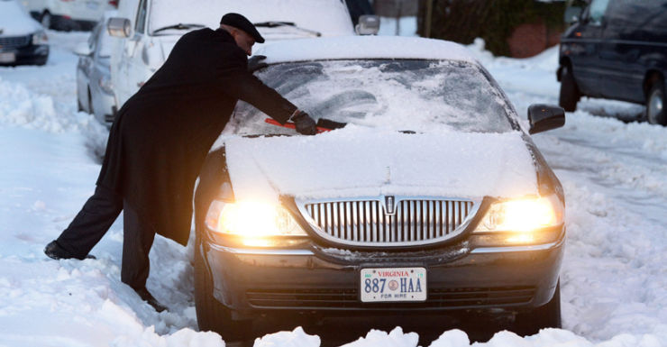 A man works to free his car from snow.