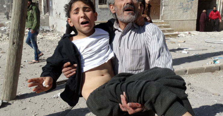 A Syrian man carried a wounded child after a reported air strike