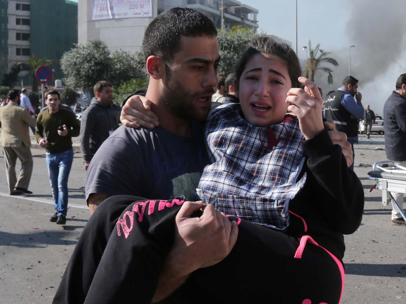 A man carries an injured girl following a bomb in Beirut