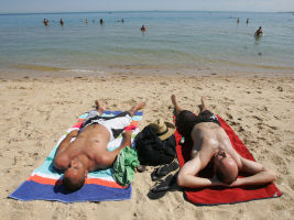 People sunbathing on a beach in Melbourne