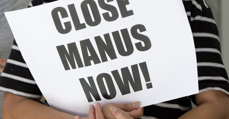 """A protester carries a sign saying """"close Manus now'."""