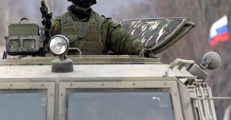 An armed man in a Russian GAZ Tigr vehicle, outside outside Simferopol
