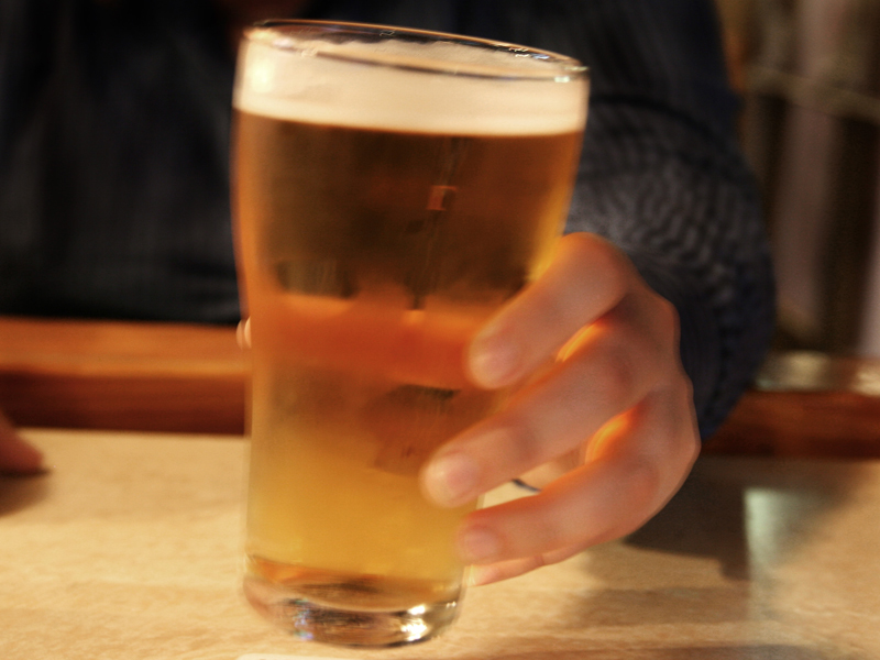 File photo of a person holding a glass of beer