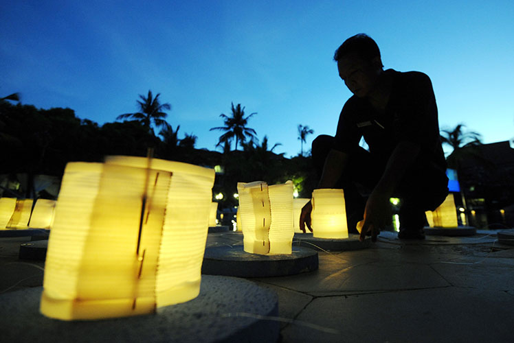 Balinese men burn lanterns during Earth Hour last year. Source: Getty