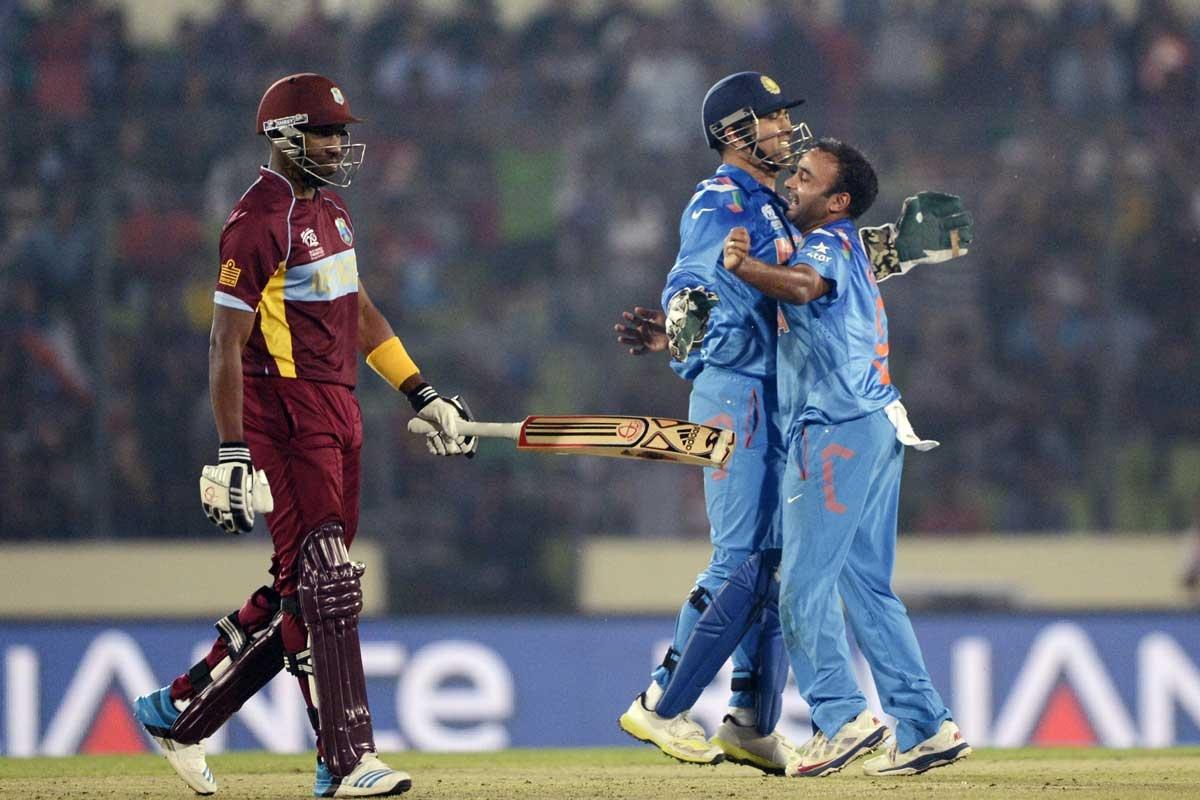 Amit Mishra (right) and MS Dhoni celebrate the dismissal of Dwayne Bravo.