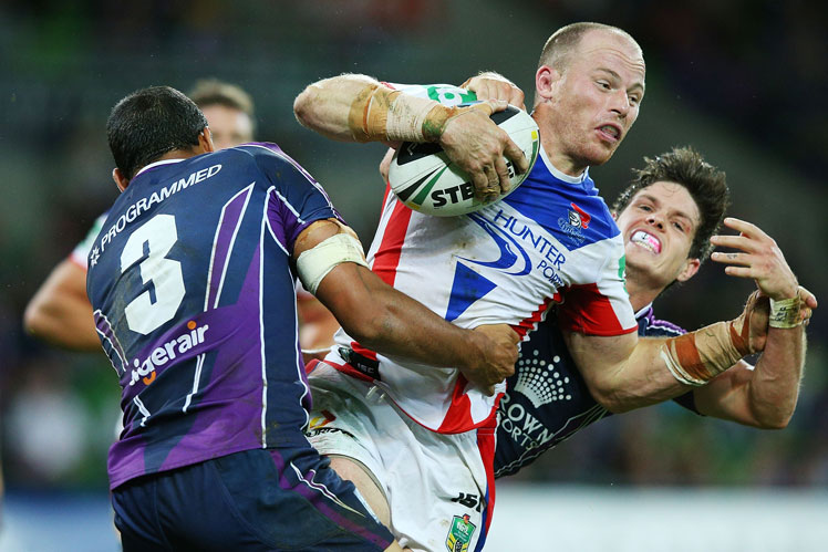 Beau Scott of the Knights is tackled by Will Chambers (left) and Ben Hampton of the Storm. Picture: Getty