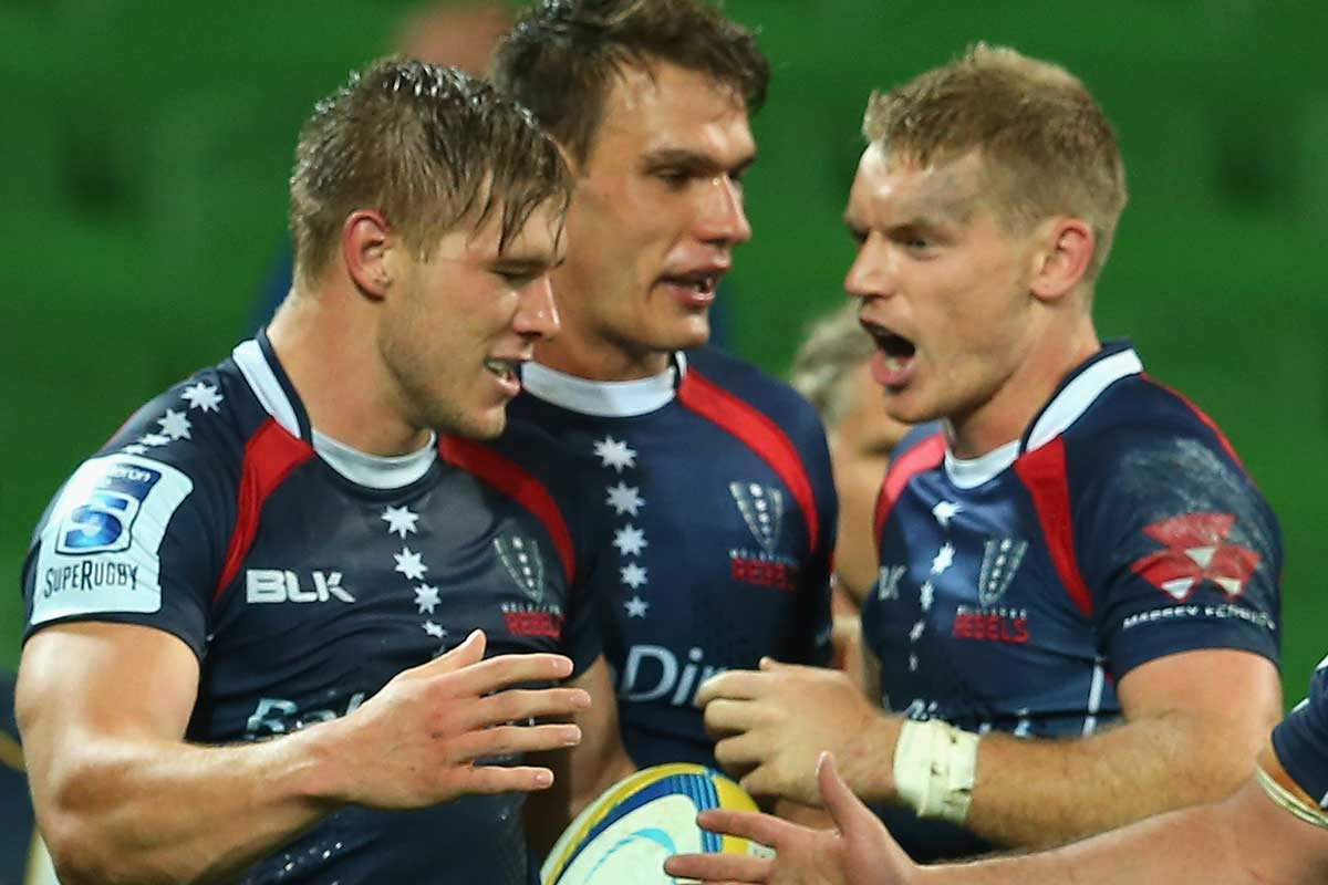 Jason Woodward of the Rebels (left) is congratulated after scoring a try.