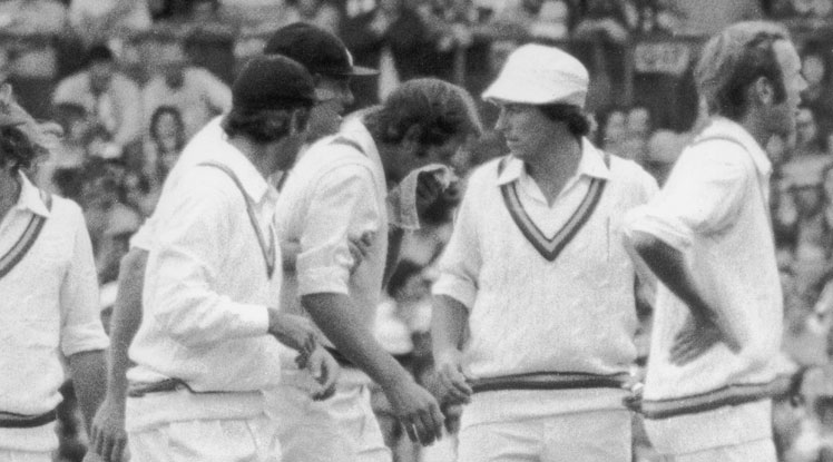 England players gather around an injured Rick McCosker.