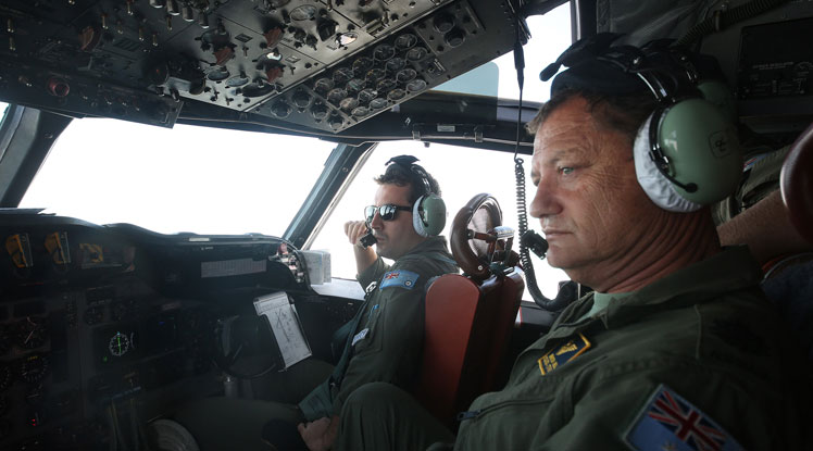 RAAF servicemen in an Orion aircraft looking for signs of the missing plane.