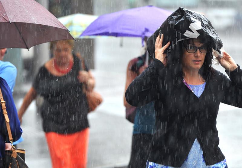 Pedestrians duck for cover as rain slams Sydney.