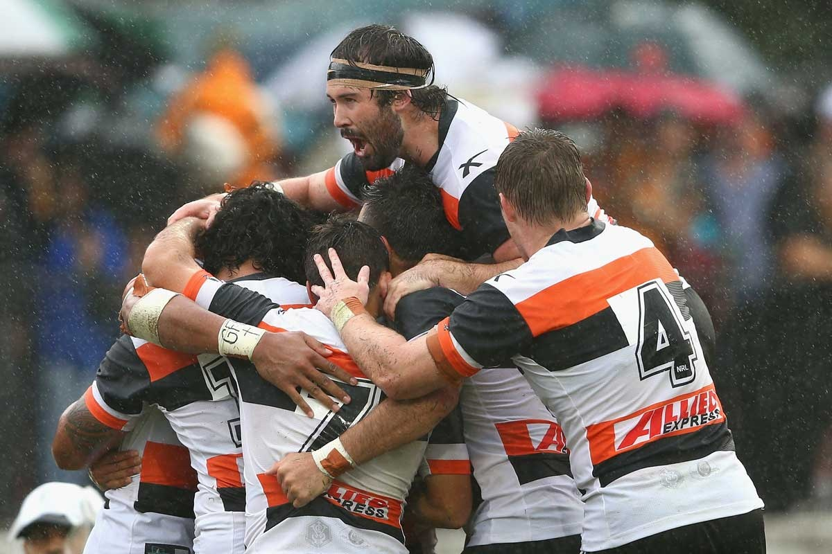 Aaron Woods and fellow Tigers mob David Nofoaluma after his try.