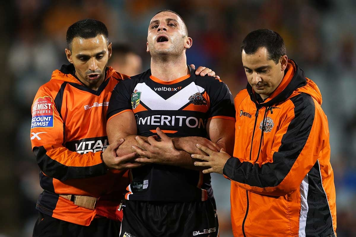 Robbie Farah is helped from the field with an elbow injury.