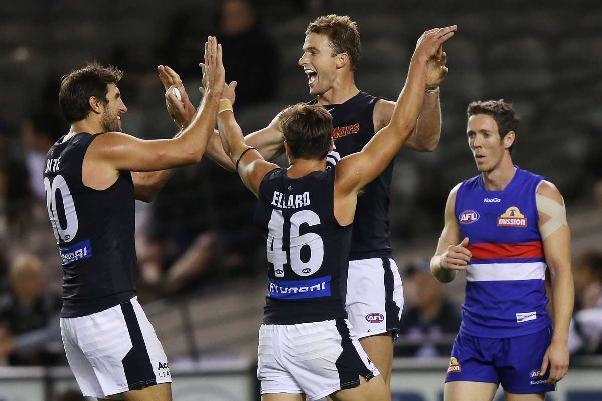 Lachie Henderson (R) of the Blues celebrates a goal with Jarrad Waite (L) and David Ellard during the round five AFL match between the Western Bulldogs and the Carlto...