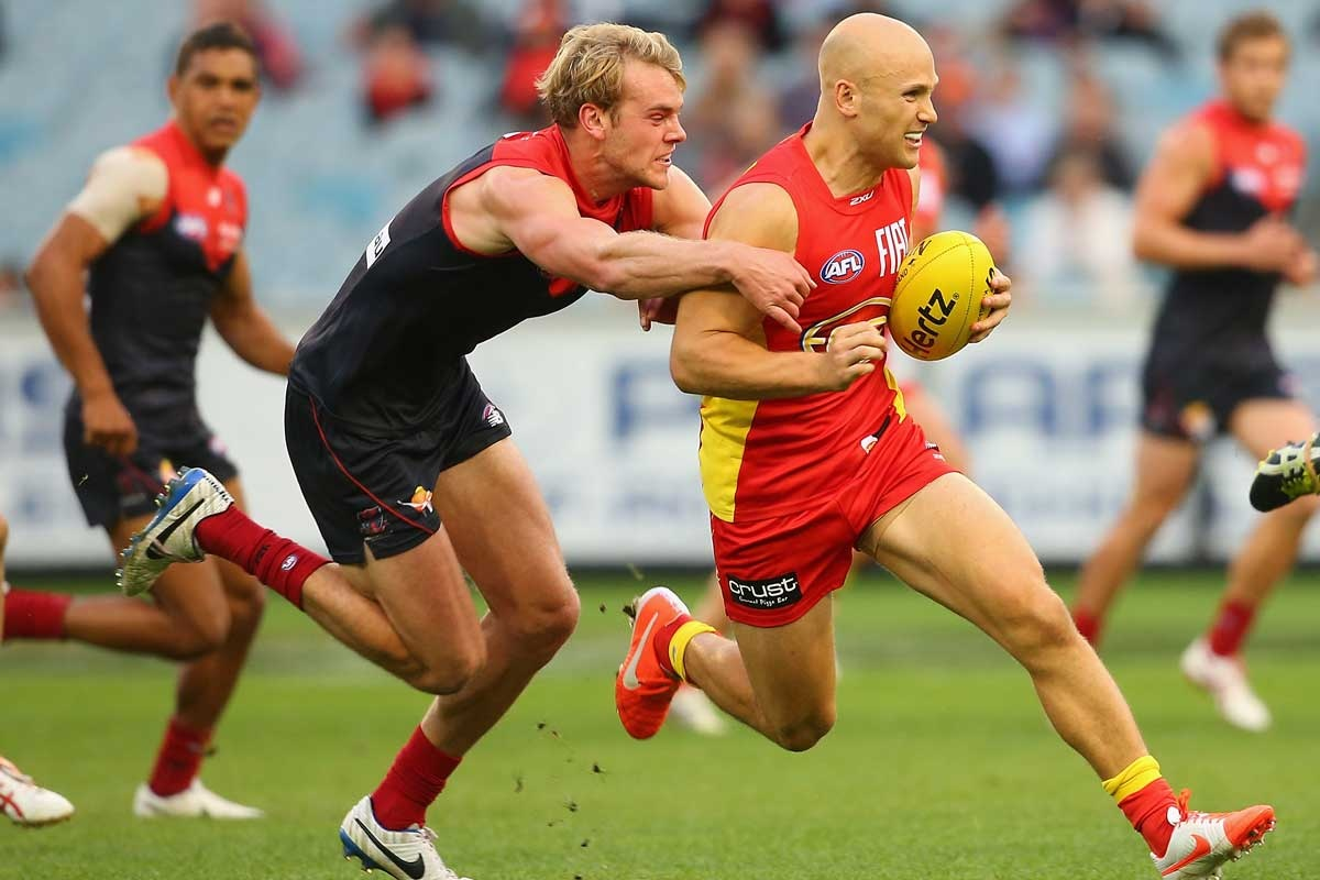 Gary Ablett of the Suns gives Jack Watts the slip.
