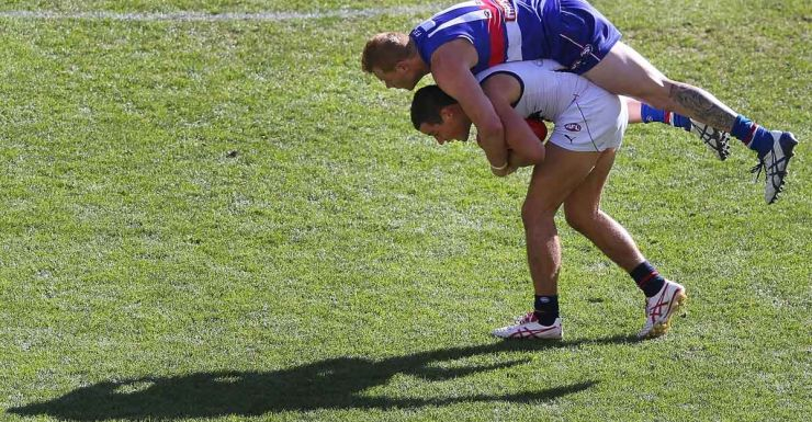Adelaide's Rory Laird is tackled by Adam Cooney.