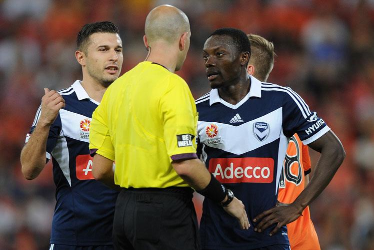 Shane Adama Traore (R) of the Victory speaks with referee Strebre Delovski during the A-League semi final against Brisbane Roar. Photo: Getty