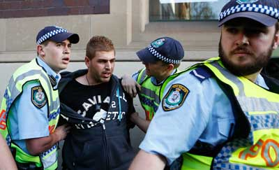 Police deal with a protester in Sydney. Photo: Getty