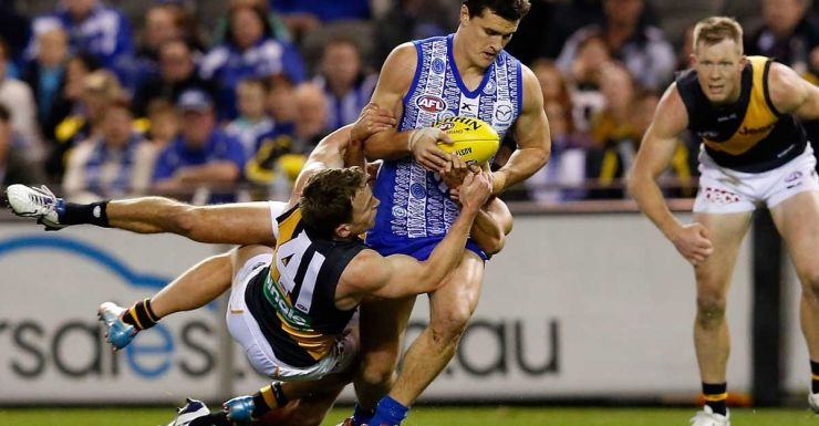 Scott Thompson fights off the attention of Nathan Foley.