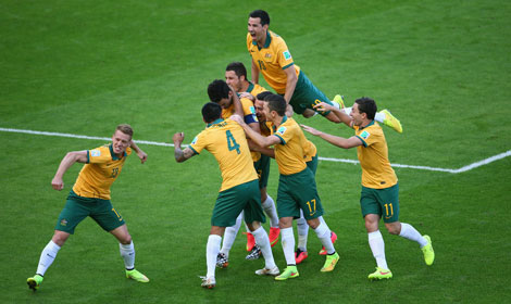 54th minute: Mile Jedinak is mobbed after converting his penalty. Photo: Getty