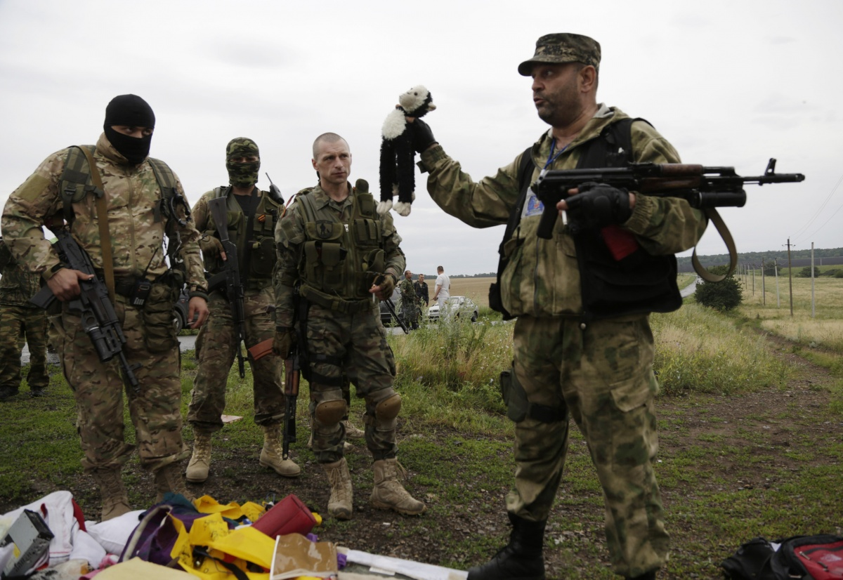 A pro-Russian rebel holds up a toy found at the crash site. Source: AAP.